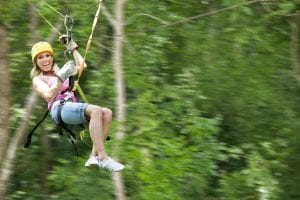 Confident woman flying through jungle